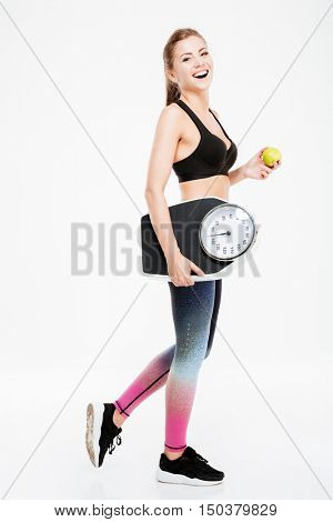 Full length portrait of a happy fitness woman holding weighing machine and green apple isolated on a white background and looking at camera