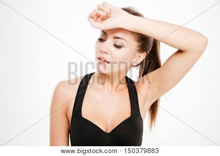 Tired fitness woman after workout wipes the sweat from her forehead isolated on a white background