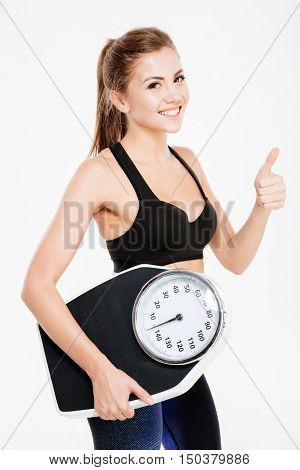 Happy young sportswoman holding weight scales and showing thumbs up gesture isolated on a white background