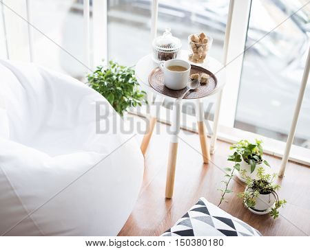 Coffee served on table in bright light scandinavian style hipster interior, cozy loft room with large windows closeup