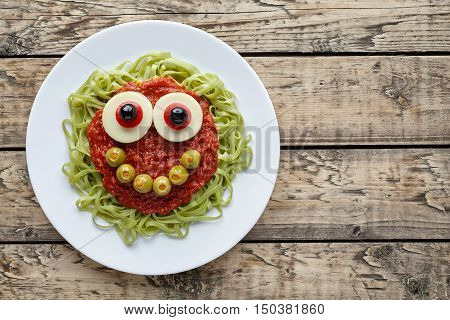 Green spaghetti pasta creative halloween food monster with cute smile, fake blood tomato sauce and big mozzarella eyeballs holiday decoration kid party meal on vintage wooden table background.