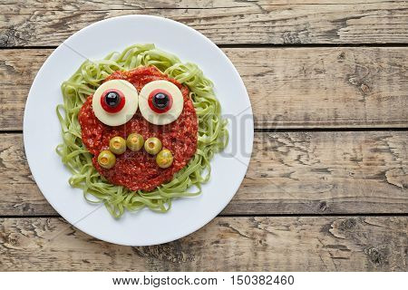 Green spaghetti pasta creative spooky halloween food monster with sad smile, fake blood tomato sauce and big mozzarella eyeballs holiday decoration kid party meal on vintage wooden table background.