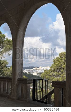 the town of Ostuni, illuminated by the sun, seen from behind an old porch