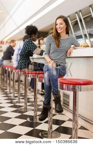View of the young woman eating in the diner