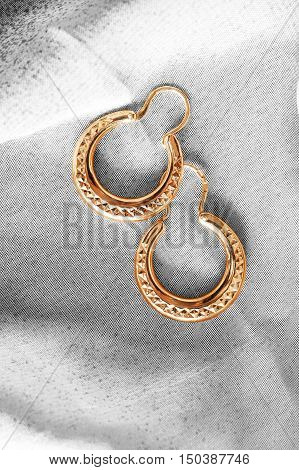 Golden ethnic earrings on white cloth as a background