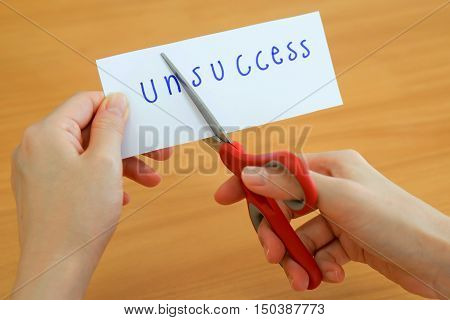 holds card with text unsuccess on wood plate
