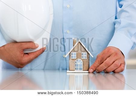 Contractor's Hands Showing Miniature House