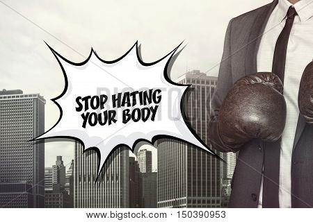 Stop hating text on speech bubble with businessman wearing boxing gloves