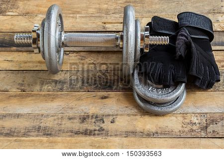 Top view of dumbbells extra weights and black gloves on the wooden floor.Sport lifestyle and fitness concept.