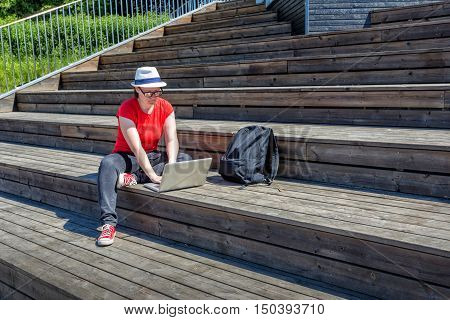 Smiling girl with glasses lying on the wooden stairs and using laptop and typing