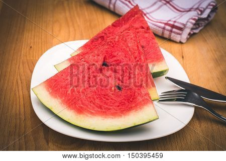 Watermelon slices on the white porcelain plate served with cutlery and napkin straw-coloured wooden background