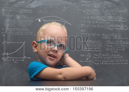 A child wearing glasses and phone on the background of school board