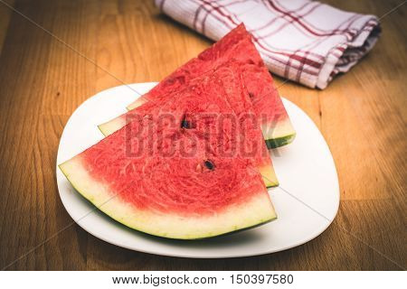 Watermelon slices on the white porcelain plate served with napkin straw-coloured wooden background