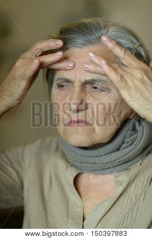 Close-up of ill elderly woman touching her head
