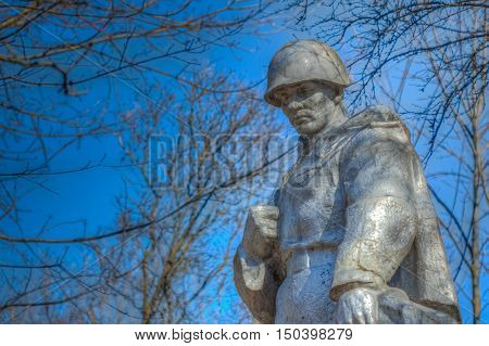 Village Khal'ch, Belarus - March 26, 2016: The monument depicts the Soviet Red Army soldier on a background of blue sky and tree branches