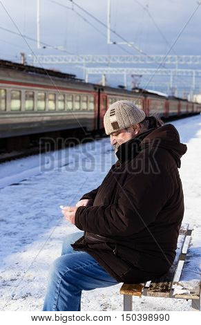 Elderly man with a phone in his hand waiting for a train on a railway platform in winter