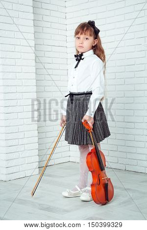 Little girl standing and holding fiddle looking at camera