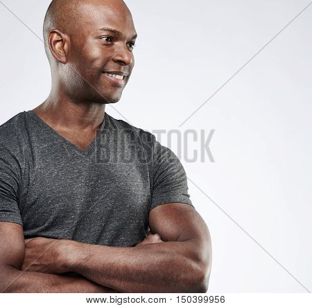 Single attractive smiling Black man with folded muscular arms looking toward copy space over gray background