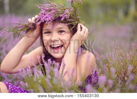 Girl is holding wreath of heather flowers, outdoor shoot