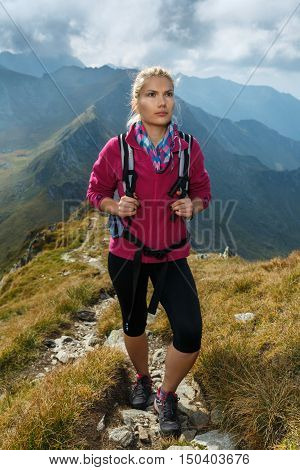 Woman Backpacker Hiking On A Trail