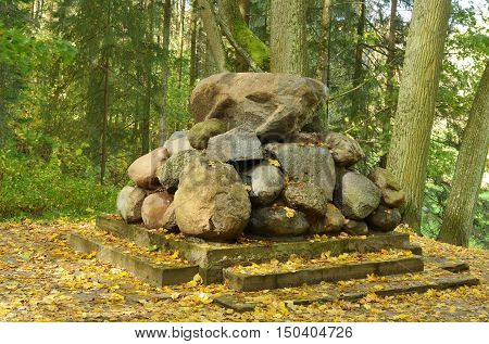 A pile of stones in the forest are collected in a cone shape.