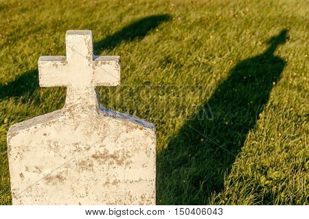 Blank headstone in a cemetery with a shadow on the grass