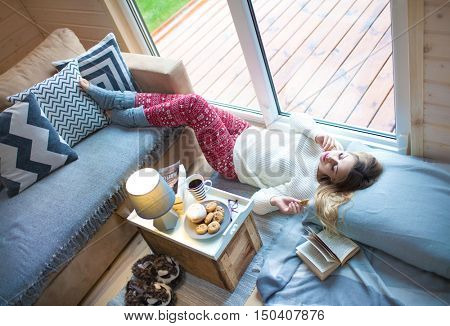 Young beautiful blonde woman with book lying down home by the living room window. Lazy cold day off concept