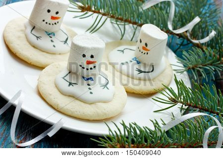 Biscuits with marshmallow and icing in the form of snowmen close up and selective focus