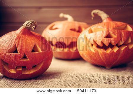 Autumn background with orange halloween pumpkins on rustic fabric