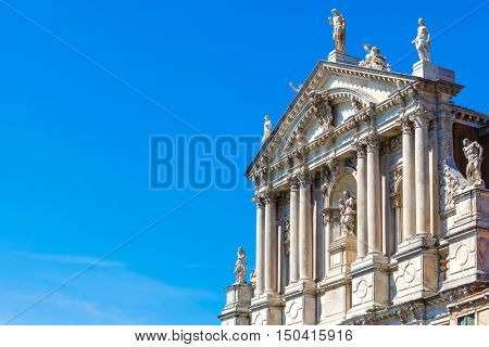 Church Scalzi. Santa Maria di Nazareth in Venice. Italy. Ancient Catholic cathedral with antique statues and columns over blue summer sky