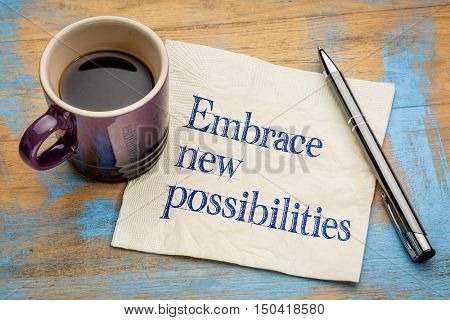 Embrace new possibilities - handwriting on a napkin with a cup of espresso coffee