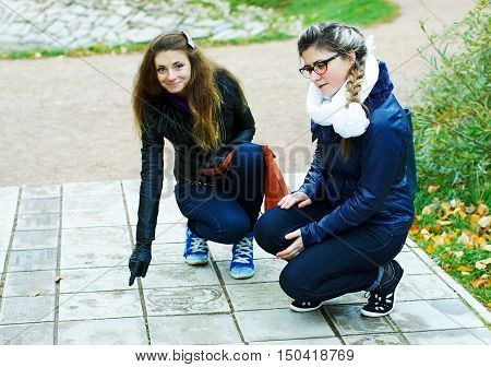Two girls walk in autumn park, squating and considering a tile on a floor
