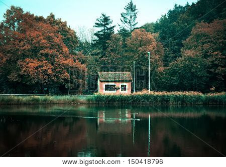 Small house at the coast of the lake. Autumn landscape