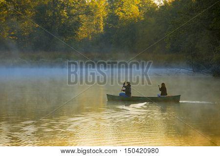 Mother and daughter canoeing through morning mist near Saluda, North Carolina