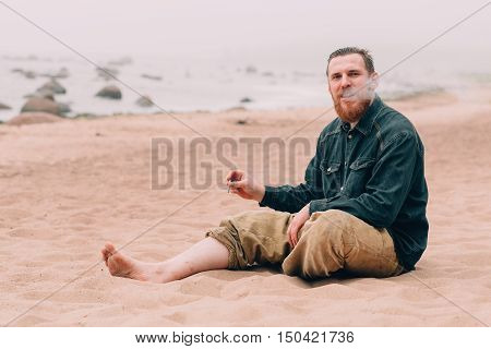 Happy bearded man smoking a cigarette on the beach. bearded hipster on the beach
