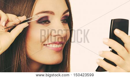 Make up and cosmetics. Woman plucking eyebrows depilating with tweezers. Attractive girl tweezing eyebrows looking at mirror