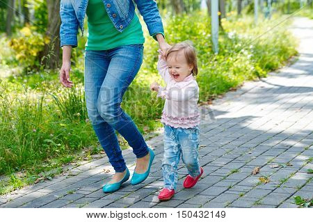 mother and laughing daughter walking outdoors in park