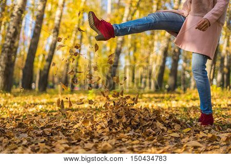 Girl kicked dry leaves. Autumn sunny day in the park. Yellow leaves underfoot.