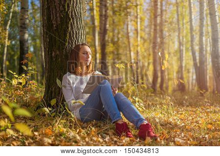 Young girl sitting under a tree with a book in hand sunny autumn day. A girl reading a book and looking thoughtfully into the distance