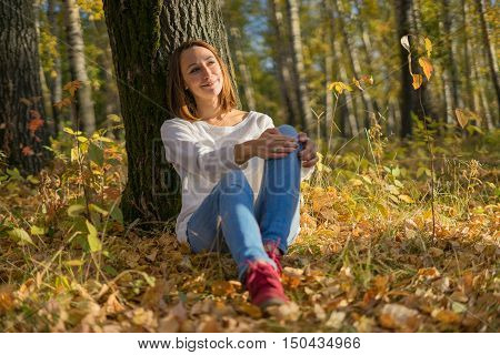 Young girl sitting under a tree in the forest sunny autumn day. Unity with nature relaxation and enjoyment