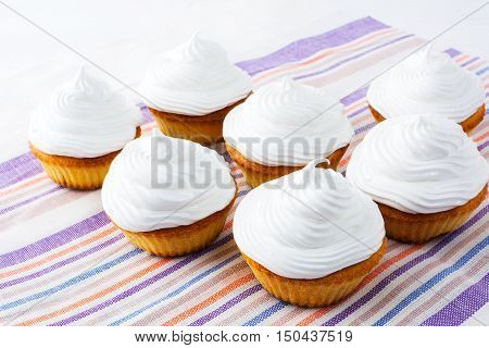 Cupcakes with white whipped cream . Homemade cupcakes with whipped cream. Sweet gourmet pastry dessert. Homemade cupcakes served for party.