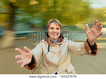 Senior Woman having fun with music headphones. background with natural motion blur
