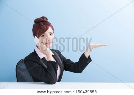 business woman talk on phone and show something with isolated on blue background asian