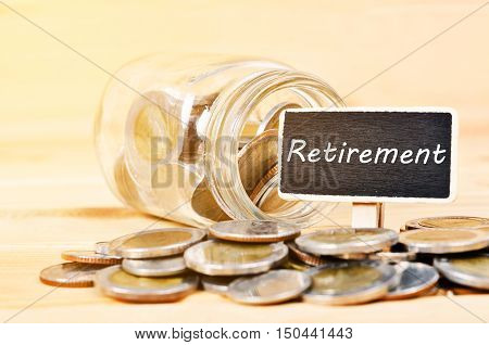 Coins and retirement plan on wooden tag.saving money concept.