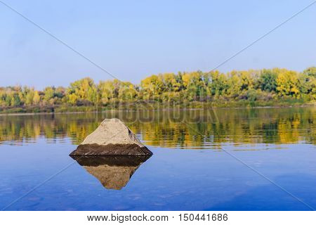 Autumn forest across the river, sunny autumn day, blue sky, backgrounnd nature