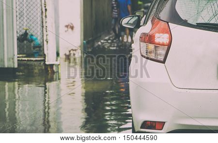 Small white car is traveling slowly in a flooded street