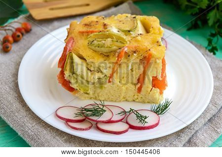 A piece of casserole of vegetables (zucchini carrots) on a white plate. Vegetarian dish. Close up