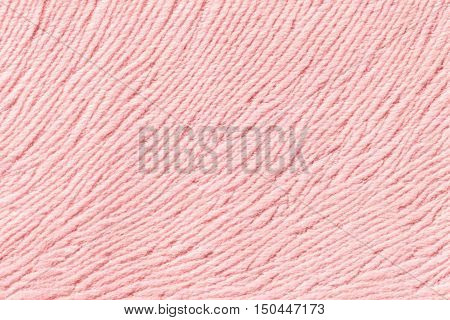 Light pink background from a soft wool textile material closeup. Fabric with natural texture. Cloth backdrop.