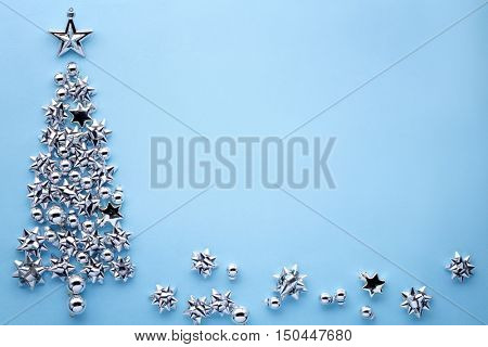 Christmas tree of glitter bows on blue background