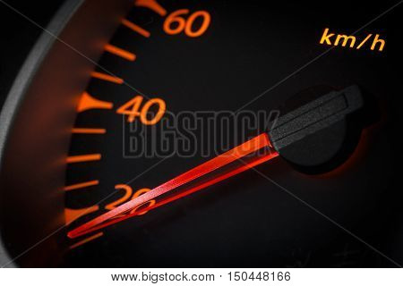 Car odometer with a red arrow closeup.